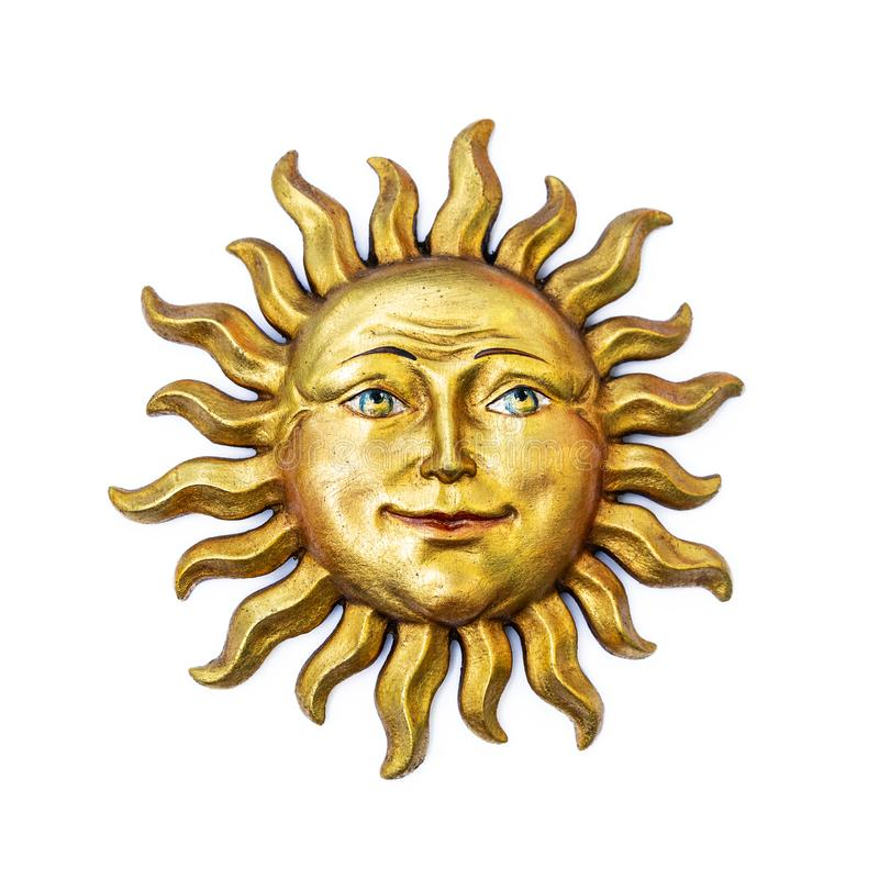 Golden sun face symbol with sunrays isolated on white. Wooden decor ornament symbol painted on gold paint. Summer stock photography