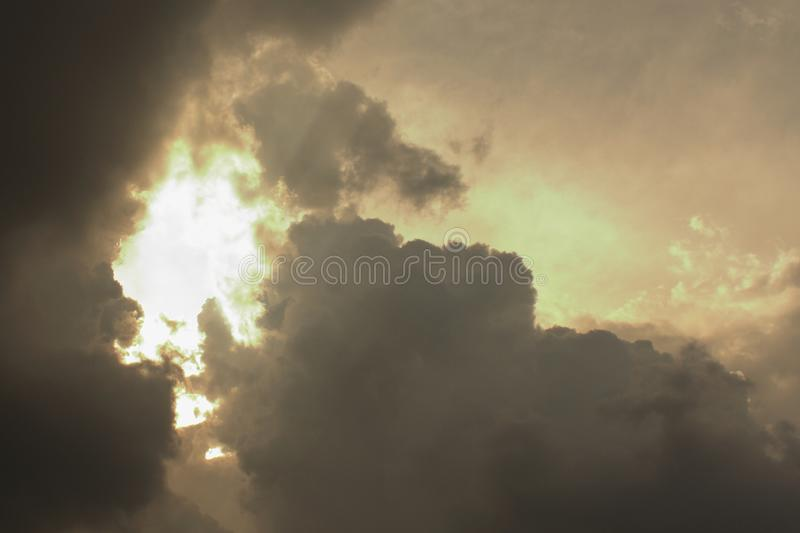 Golden sun ray shining through the dark gray clouds. royalty free stock images