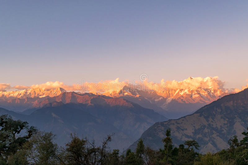 Golden sun rays falling on snow cladded peaks of Gangotri group of Garhwal Himalayas during sunset from Deoria Tal. stock photo