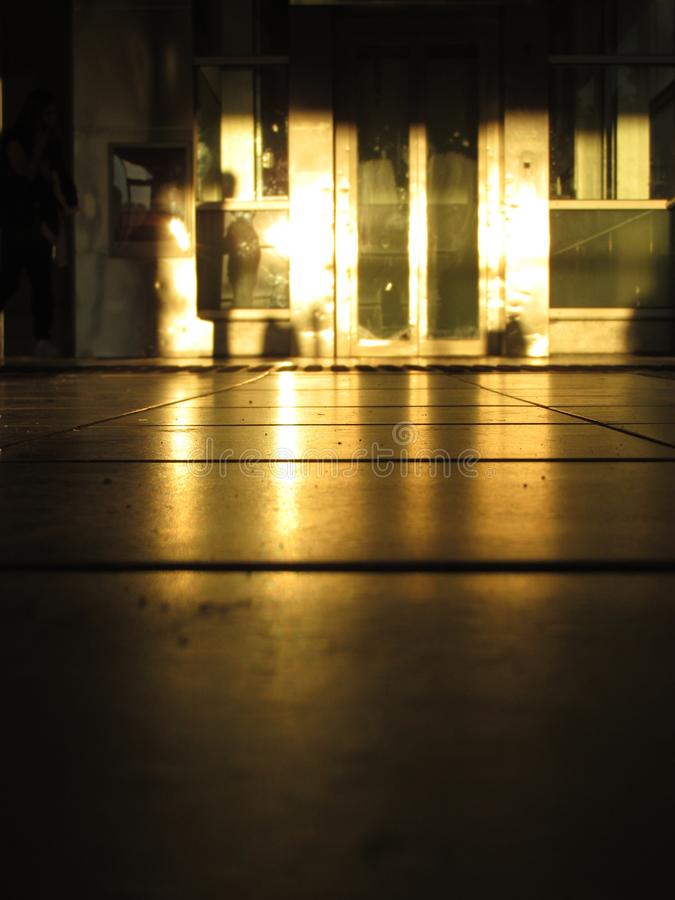 Golden sunlight reflecting off an elevator door at a train station stock images