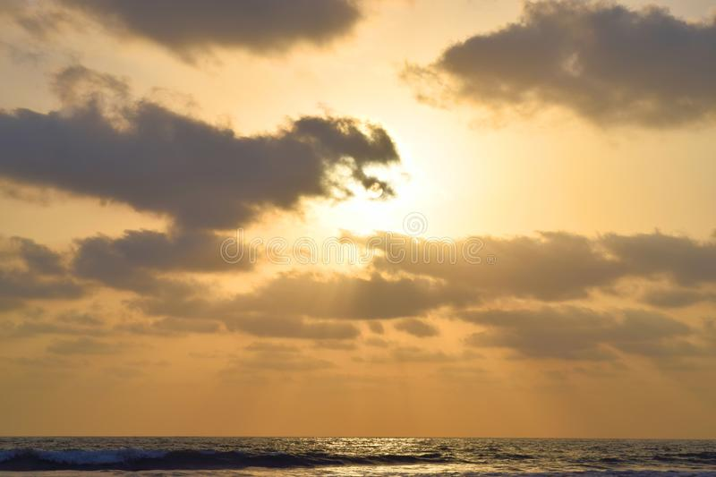 Golden Sunrays coming through Dark Clouds over Sea at Evening stock photography