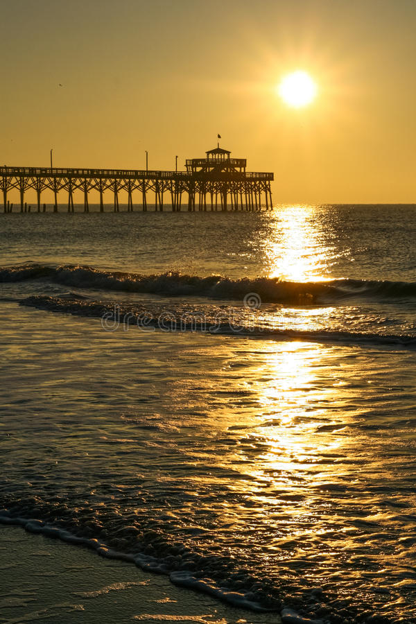 Golden Sunrise Cherry Grove Pier Myrtle Beach. A beautiful golden sunrise over the famous landmark Cherry Grove ocean beach pier, reflecting off the water in royalty free stock image