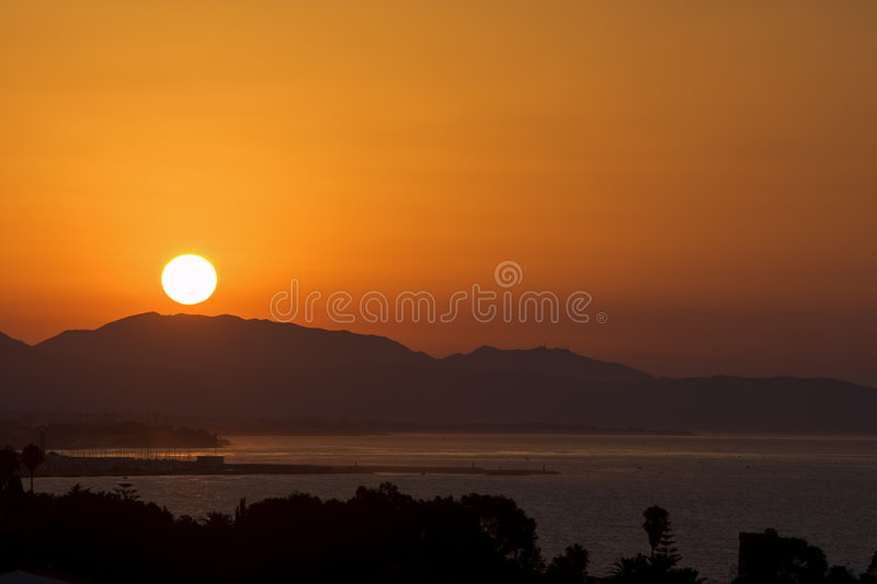 Golden sunrise over port of Marbella royalty free stock photography