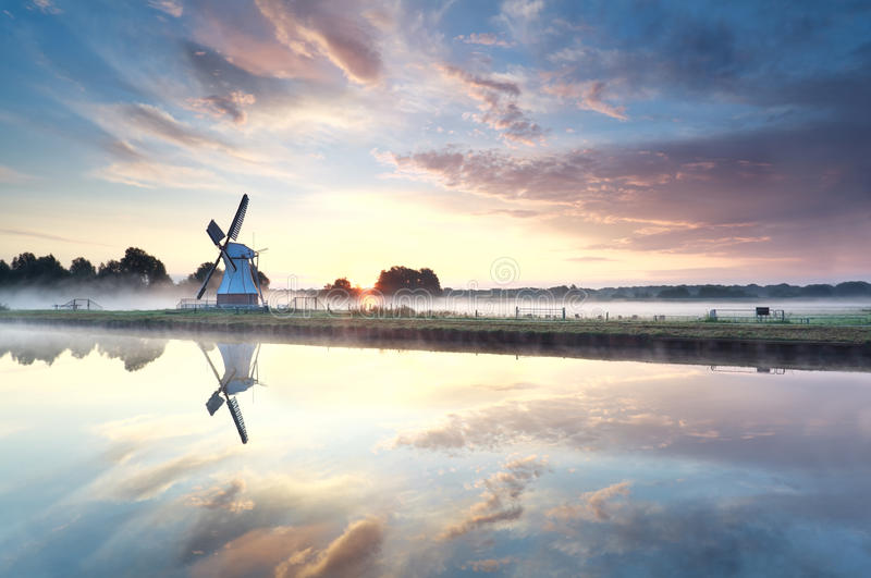 Golden sunrise over windmill reflected in river stock photos