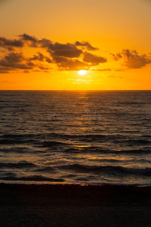 A golden sunrise with reflection on the Atlantic Ocean on Delray Beach, Florida. A golden sunrise through the clouds with reflection on the Atlantic Ocean on stock image