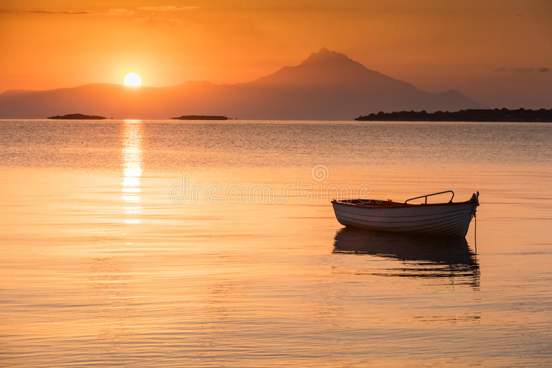 Golden Sunrise. Small fishing boat in the calm Greek bay at sunrise stock photos