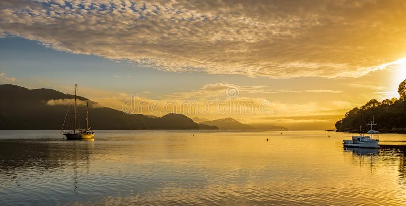 A golden sunset across the Marlborough Sound, will calm waters and several boats in the foreground. Nobody in the image royalty free stock photos
