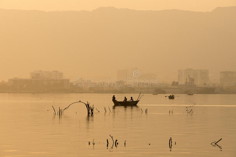 Golden sunset at Ana Sagar lake in Ajmer, India. With silhouettes of trees and fisherman royalty free stock images