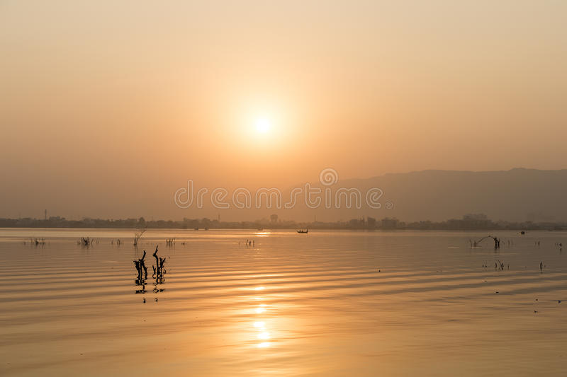 Golden sunset at Ana Sagar lake in Ajmer, India. With silhouettes of trees and fisherman stock photos