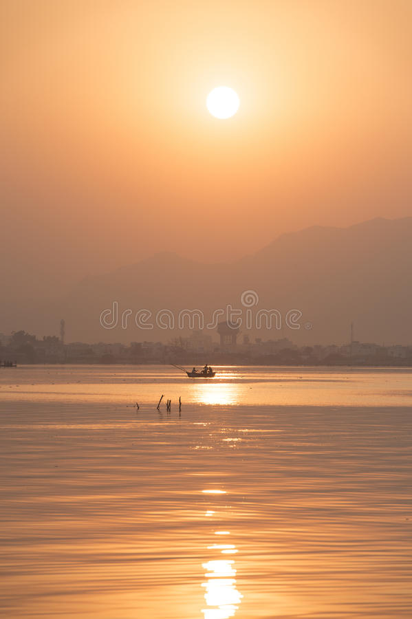 Golden sunset at Ana Sagar lake in Ajmer, India. With silhouettes of trees and fisherman stock images