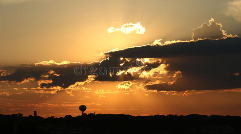 Golden sunset with clouds over land. Sun peeks thru clouds during sundown royalty free stock image