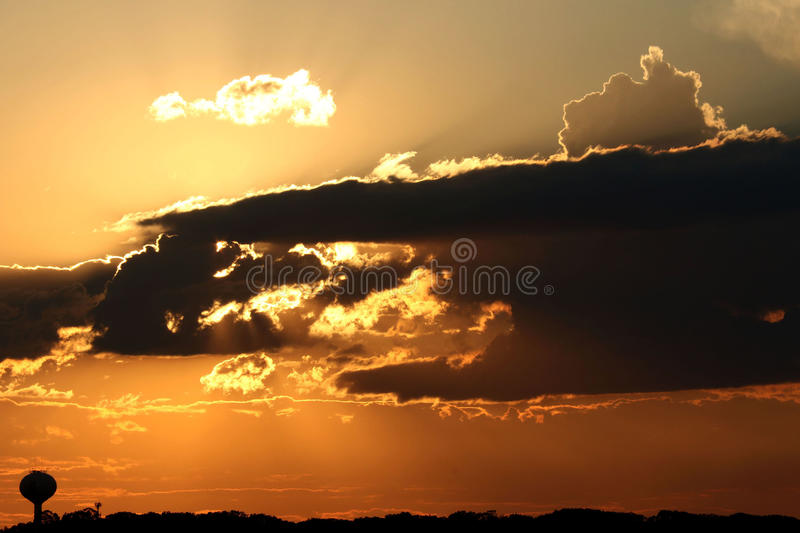 Golden sunset with clouds with water tower. Sun peeks thru clouds during sundown stock photography
