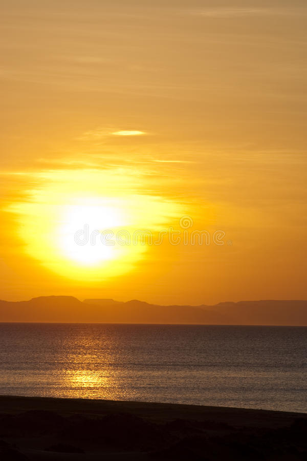Golden sunset over beach and mountain horizon stock images