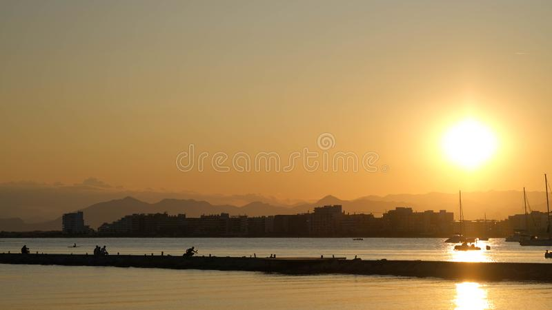 Golden sunset over the coastal city in the summer time stock photos