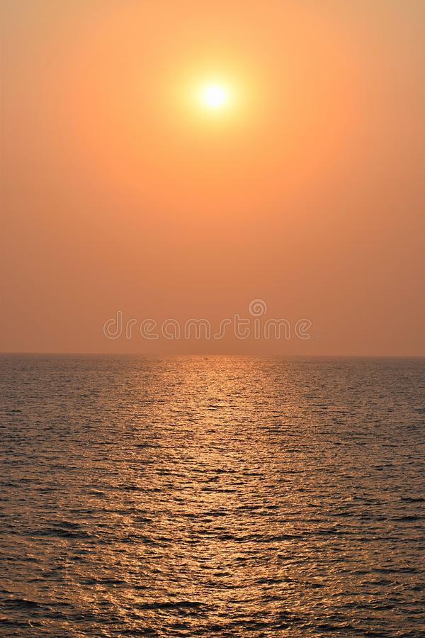 Golden Sunset over Infinite Ocean. This is a photograph of setting sun with its golden-yellow rays... The bright yellow reflection is seen over water of infinite stock photo