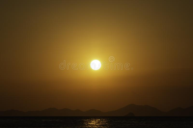 Golden sunset over the sea, mountain lines at background. Eighty percent of copy space in the picture.  stock photos