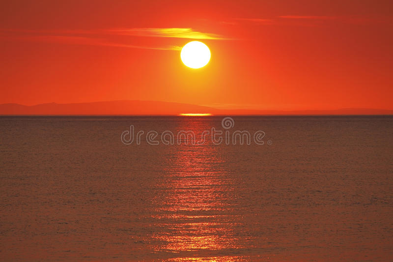 Golden sunset over water. Golden sun sunset over water causing glittering trail stock images