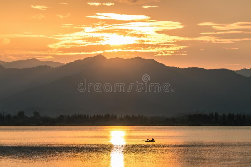 Golden sunset scene of lake and mountains stock images