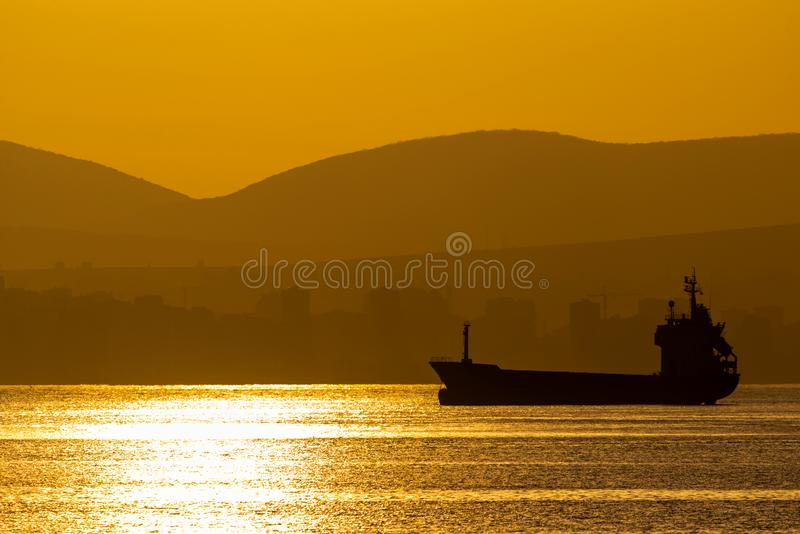 Golden sunset, silhouette of the city and cargo ship. Beautiful architecort by the sea on the background of the sunset stock photo