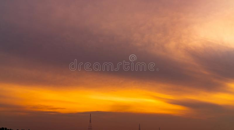 Golden sunset sky over high voltage electric tower. Golden sky and white clouds. Beautiful cloudscape. Nature background. stock image