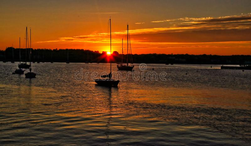 Golden sunset Stonington Connecticut sailboats. Golden sunset and sailboat silhouettes with reflections on ocean in Stonington Connecticut stock images