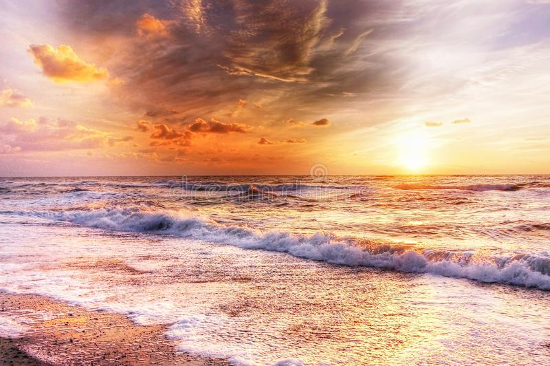 Golden sunset with waves on the sea shore stock photo