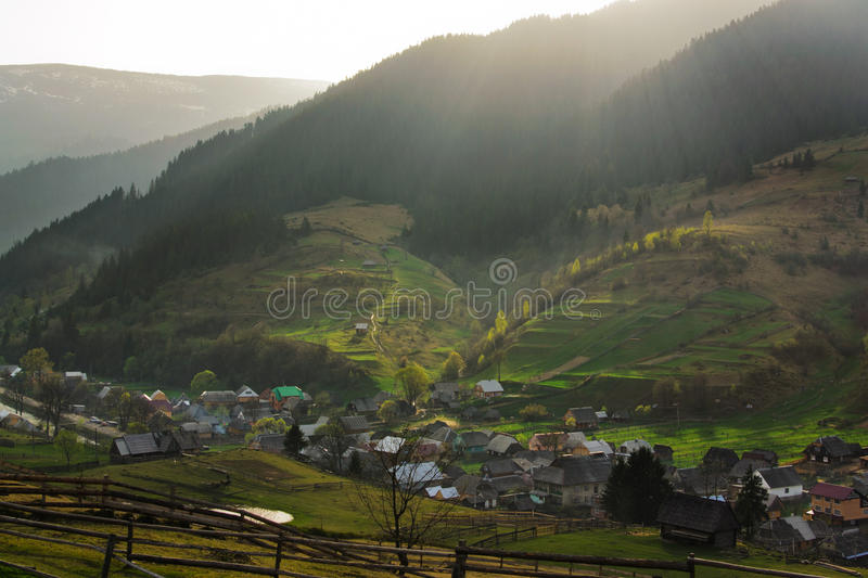 Golden sunshine of Carpathian. Rural landscape with village houses and mountains. Spring of Carpatian. Panorama royalty free stock image