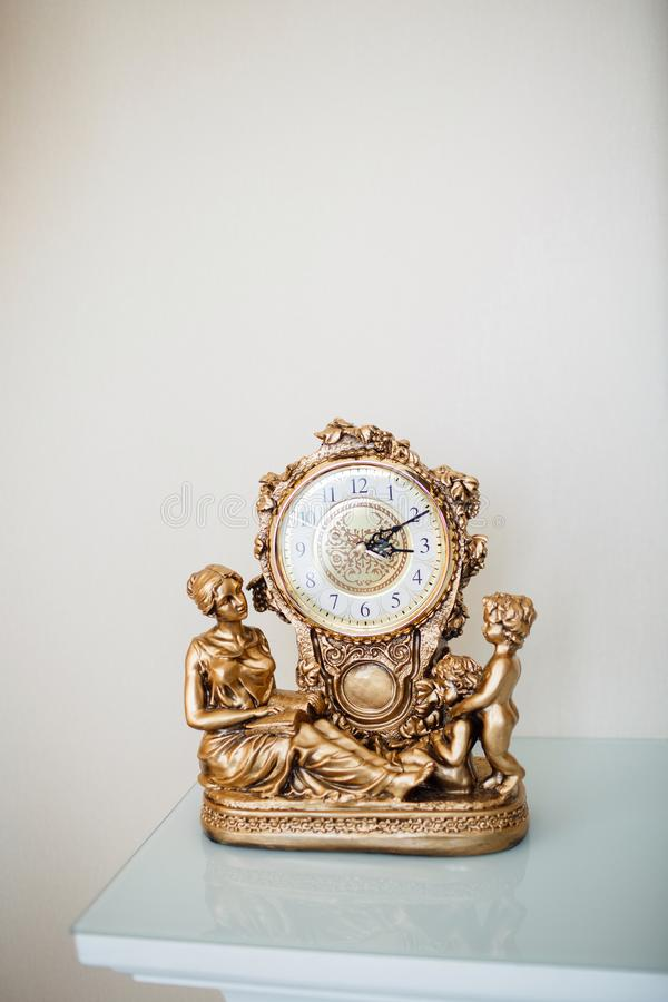 The golden table clock is decorated with figures of a woman of two boys. royalty free stock photos