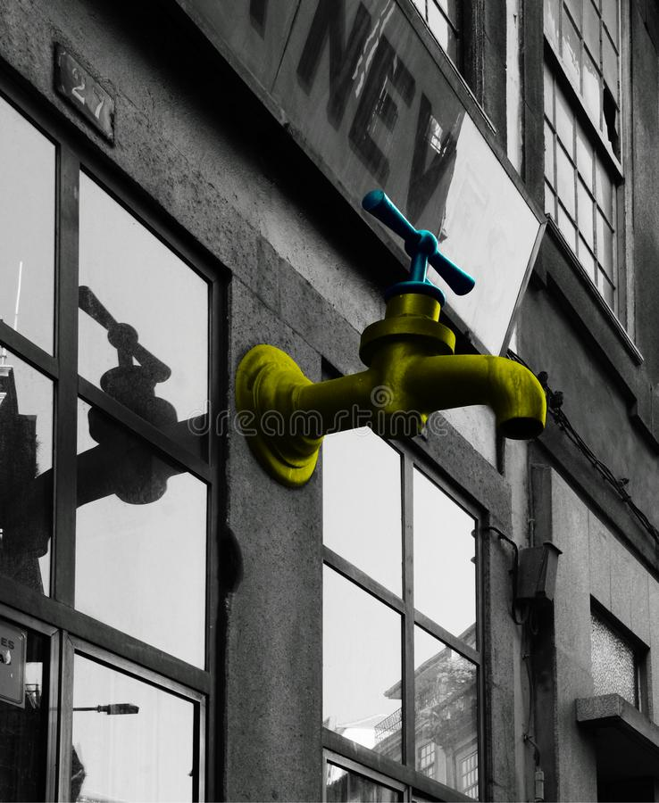 Golden tap on the facade. Shot in black and white  and painted in colors detail on the facade of this historic building representing some character, animal or royalty free stock images