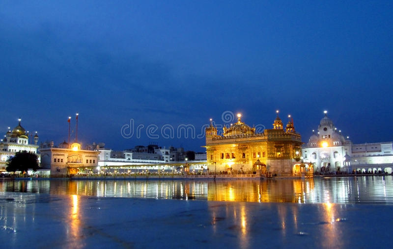 Golden Temple Amritsar, India at night. People in a line to a holy book Harmandir Sahib - Golden Temple, in Amritsar, India. The holy place of worship of the stock photography