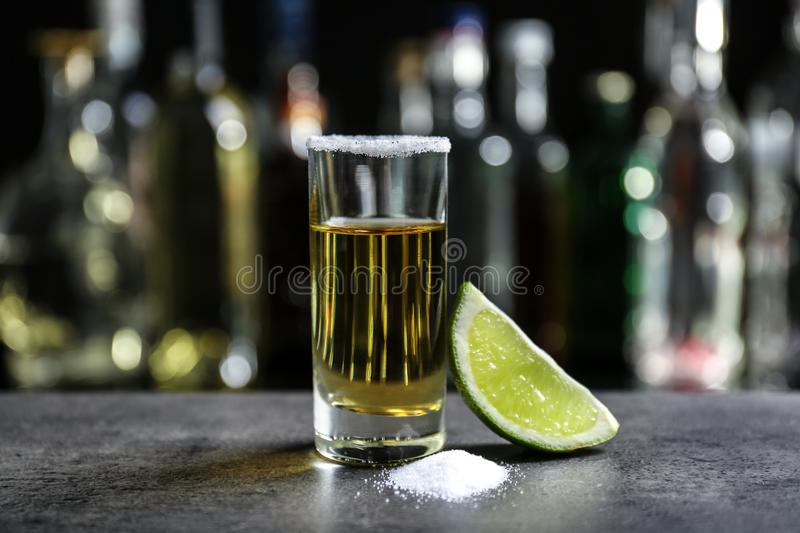 Golden tequila shot with juicy lime and salt. On blurred background of glass bottles stock photo
