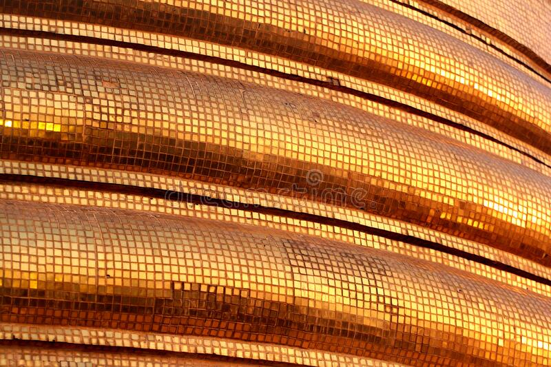 Golden tiles of a Buddhist stupa, Thailand. Abstract Southeast Asian background royalty free stock photography