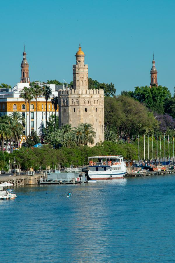 Golden tower Torre del Oro along the Guadalquivir river in Sevilla in a beautiful summer day, Spain royalty free stock image