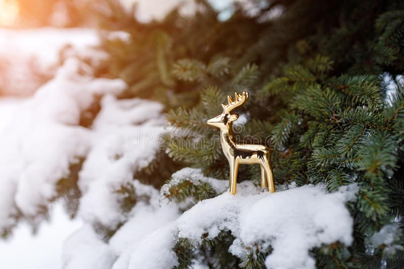 Golden toy deer stands on a snowy branch of evergreen pine as a symbol of the New Year holiday.  stock photography