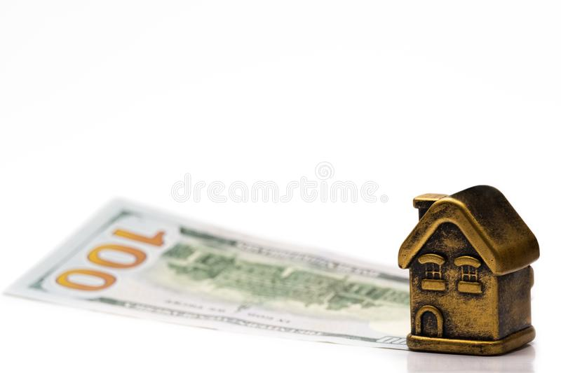 A golden toy house stands on a 100 US dollar bill. Concept mortgage, loan, pledge, financial investment or sale of real estate. royalty free stock images