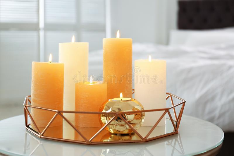 Golden tray with burning candles on table. In bedroom stock image