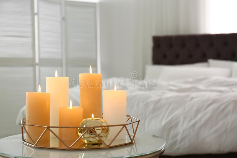 Golden tray with burning candles on table. In bedroom stock photos