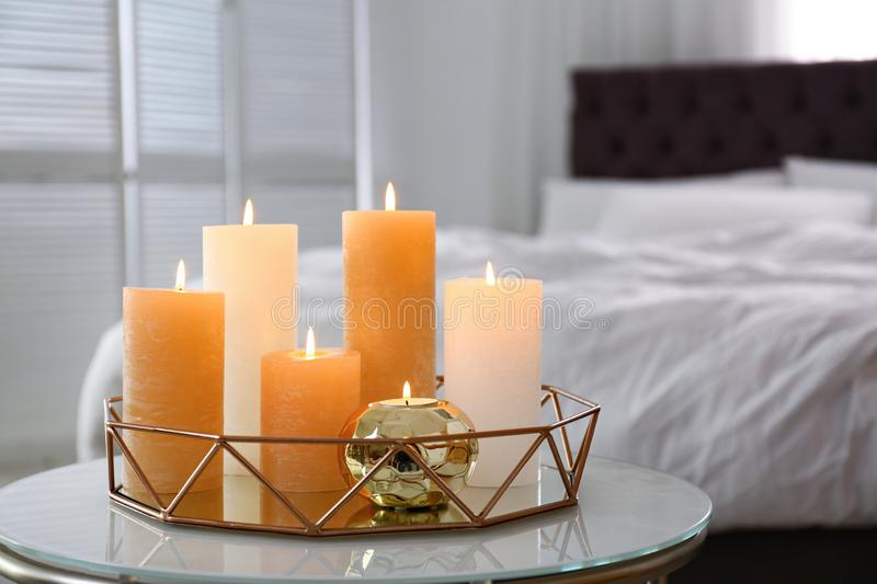 Golden tray with burning candles on table. In bedroom royalty free stock images