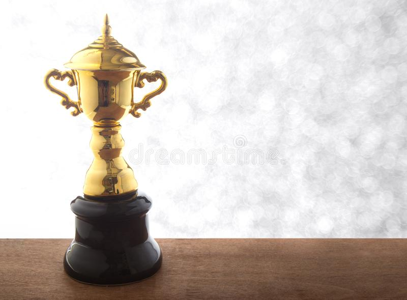 Golden trophy on wooden table over abstact white bokeh background. Winning awards with copy space. Golden trophy on wooden table over abstact white bokeh royalty free stock photography