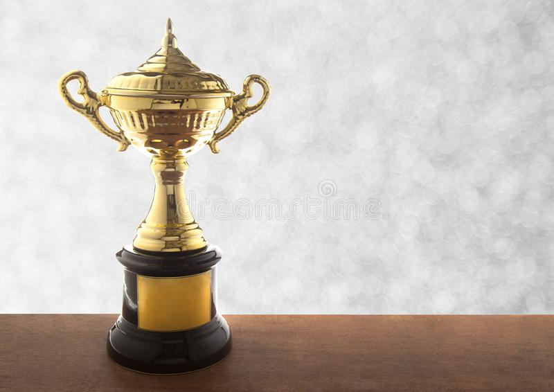 Golden trophy on wooden table over abstact white bokeh background. Winning awards with copy space. Golden trophy on wooden table over abstact white bokeh stock photos