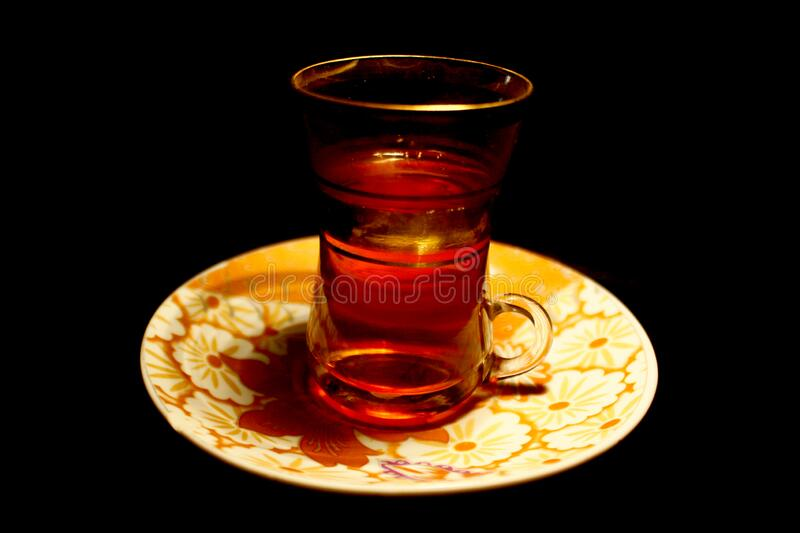Golden turkish cup of tea isolated on black stock photography