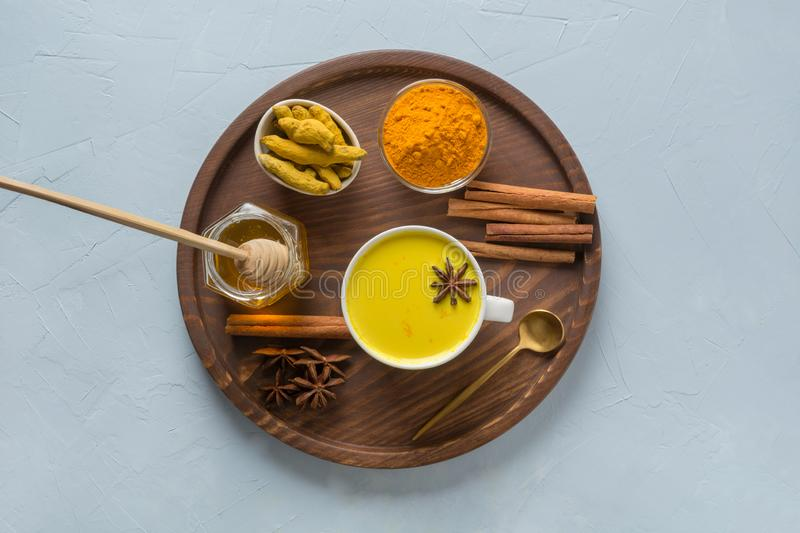 Golden turmeric milk with curcuma powder, honey and spices on light blue background. Healthy drink for immunity. View from above royalty free stock photo