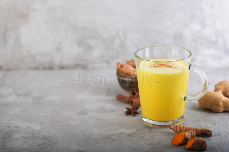 Golden turmeric milk on the gray background with ingredients royalty free stock image