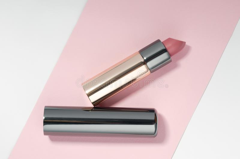 Golden und rosa Farbelippenstift auf Rosa- und weißemhintergrund chromieren lizenzfreie stockfotos