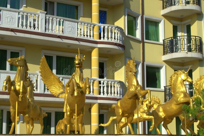 Golden unicorns kitschy decoration. Golden unicorns in front of pretentious hotel facade in Bulgarian summer resort Elenite stock photo