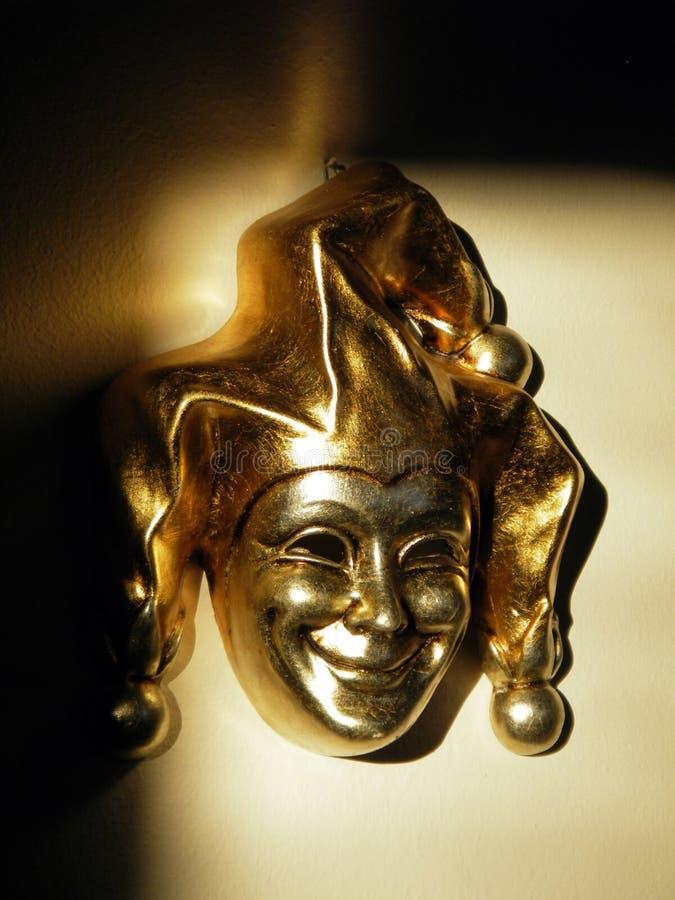 GOLDEN VENETIAN MASK. Of smiling harlequin royalty free stock photo