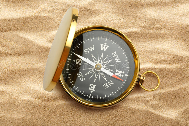 Golden vintage compass on sand stock photography