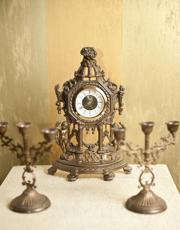 Golden vintage metallic clock with two candlesticks for three candles on white table. Luxurious art objects stock photos