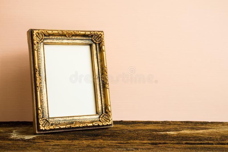Golden vintage photo frame on old wooden table over pink wall ba royalty free stock photography