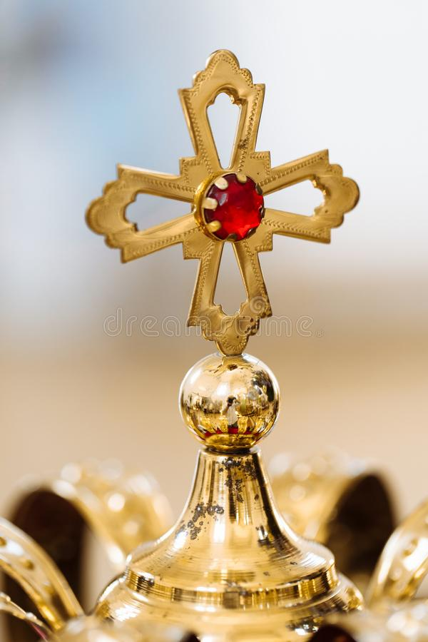 Golden wedding crowns with precious stones lying on the table in the church. Golden cross with red stone stock image